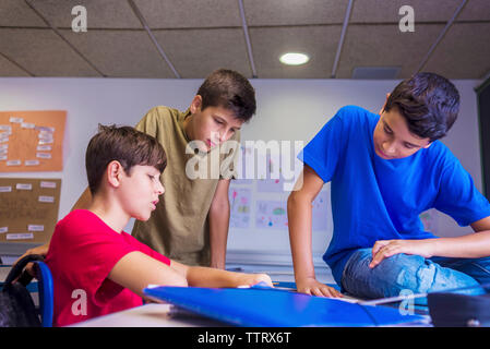 Friends discussing in classroom - Stock Photo