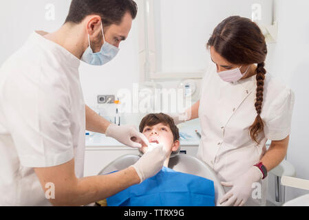 Dentist examining patient's teeth by assistant in medical clinic - Stock Photo