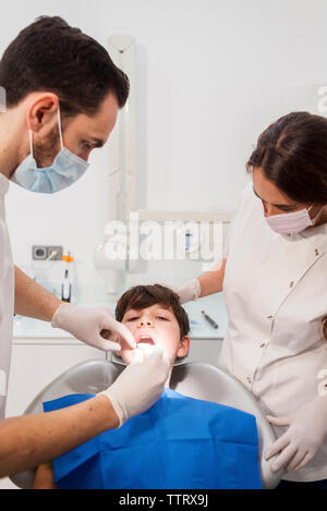Assistant and dentist examining patient's teeth in medical clinic - Stock Photo