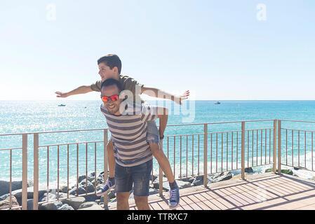 Father holding piggyback his son while walking along seashore
