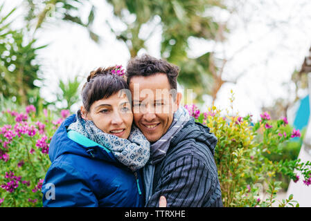 Portrait of happy mid-adult couple hugging and smiling outdoors - Stock Photo