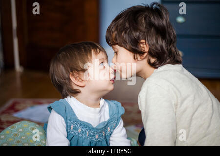 Close-up of brother kissing cute sister on nose while sitting at home - Stock Photo