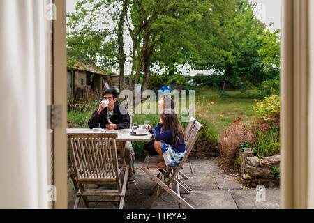Family having breakfast in yard seen through window - Stock Photo