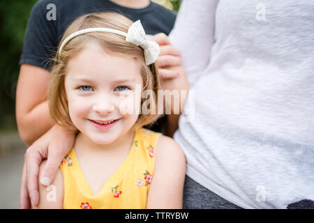 Portrait of cute girl standing with family in yard
