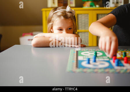 Cute girl looking at sister playing ludo on table in house - Stock Photo