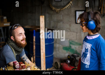 High angle view of blacksmith talking to boy in workshop - Stock Photo