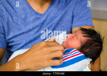 a pink-cheeked baby girl lays sleeping cradled in her father's arms - Stock Photo