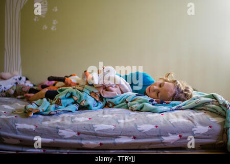 a happy little girl snuggles in bed with her stuffed animals - Stock Photo