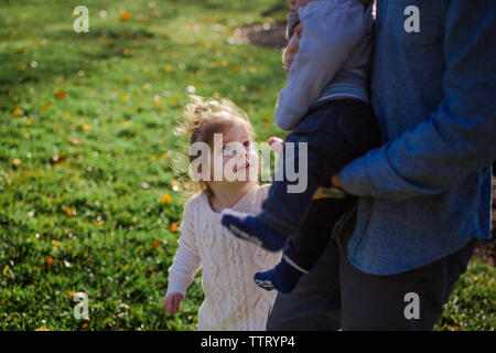 A little girl looks up at her baby brother held in her father's arms - Stock Photo