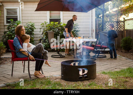 a family sits on their patio preparing dinner together - Stock Photo