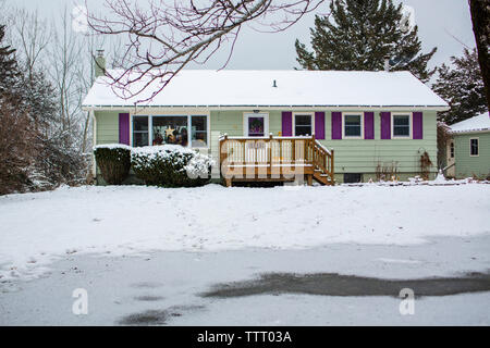 Front view of a cheerful house in a snowy yard with children in window - Stock Photo