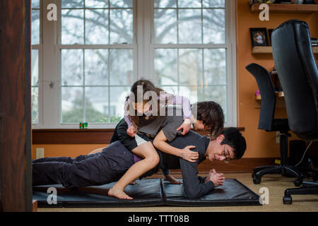 A father holds a yoga position with two children piled on his back - Stock Photo