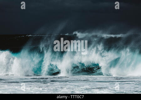 Scenic view of waves splashing in sea against sky - Stock Photo