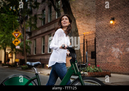 Young woman walking with bicycle on street - Stock Photo