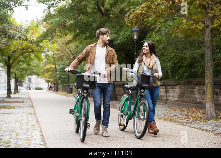 Couple talking while walking with bicycle on road at park - Stock Photo