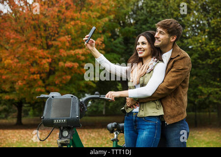 Happy couple taking selfie while standing with bicycle in park - Stock Photo