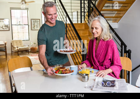 Man setting plates on dining table by woman at home - Stock Photo