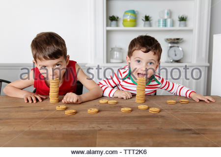Goofy boys at kitchen table eating stack of cookies - Stock Photo