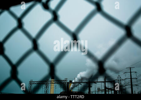 Smoke emitting from factory seen through chainlink fence against sky - Stock Photo