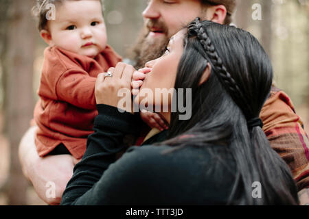 Mother kissing daughter's hand being carried by father in forest - Stock Photo