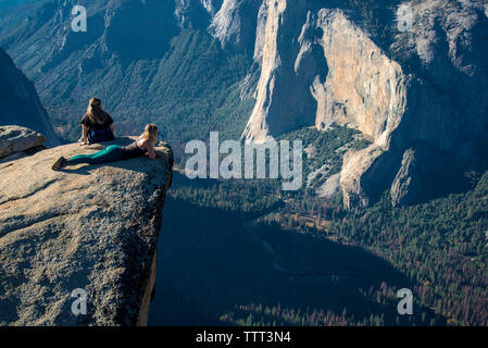High angle view of female friends relaxing on cliff at Yosemite National Park - Stock Photo