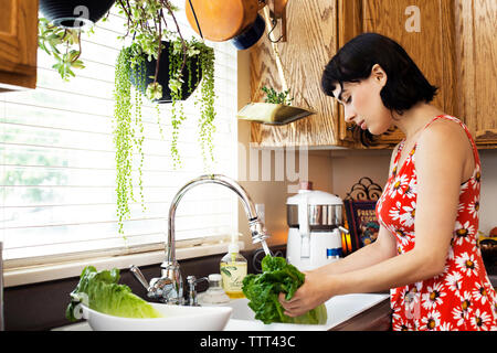 Side view of woman washing lettuce in kitchen sink - Stock Photo