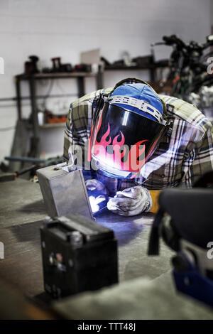Mechanic welding metal at auto repair shop - Stock Photo