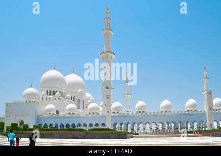 Exterior of Sheikh Zayed Mosque against clear blue sky during sunny day - Stock Photo