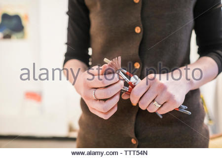Midsection of female painter holding paintbrushes while standing in art studio - Stock Photo