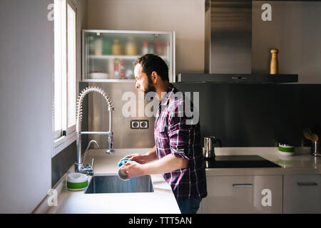 Man with beard and plaid shirt washing dishes at home.