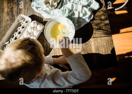boy making scrambled eggs - Stock Photo