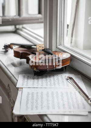 High angle view of violin with sheet music and bow on window sill in mansion - Stock Photo