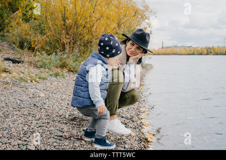 Mother with cute son enjoying at lakeshore against cloudy sky in park during autumn - Stock Photo