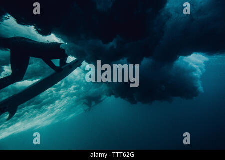 Underwater view of a surfer duck-diving - Stock Photo