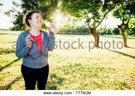 Happy sportswoman drinking water at park - Stock Photo
