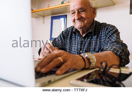 Senior man writing on graphics tablet while using laptop computer at office - Stock Photo