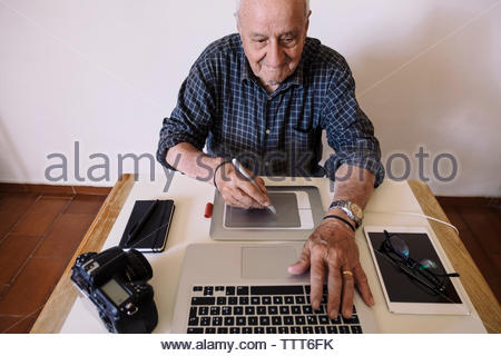 High angle view of senior man writing on graphics tablet while using laptop computer at office - Stock Photo