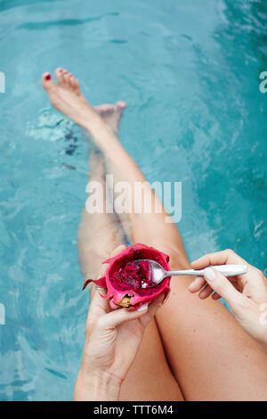 Overhead view of woman eating dragon fruit by swimming pool - Stock Photo