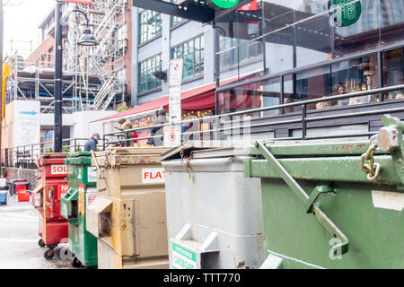 Vancouver, BC, Canada: Industrial size garbage containers in Yaletown. Some are unlocked. On the street awaiting garbage pick-up - Stock Photo