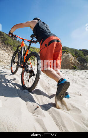 Low angle view of athlete with bicycle walking on sand against clear blue sky - Stock Photo