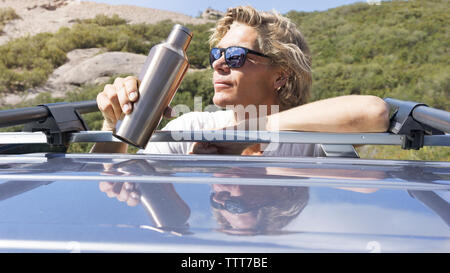 Man in sunglasses drinking water while leaning on car - Stock Photo