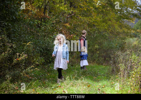little girl walking away from dad and sister in woods wearing a dress - Stock Photo