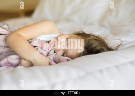 High angle view of baby boy with toys sitting in kitchen sink - Stock Photo