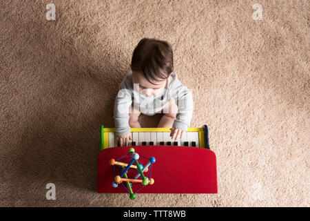 Overhead view of baby boy playing toy piano on carpet at home