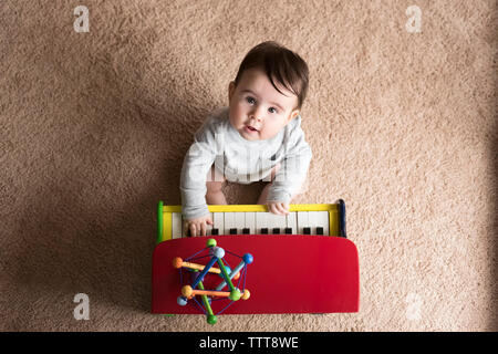 Overhead portrait of cute baby boy playing toy piano on carpet at home