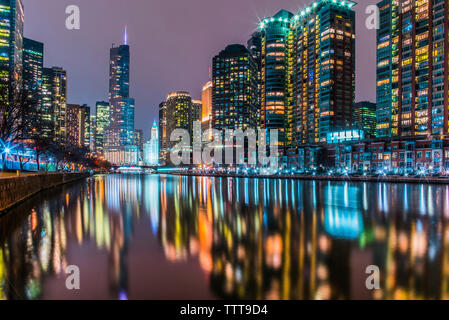 Illuminated modern buildings reflecting on calm Chicago River against sky at night - Stock Photo