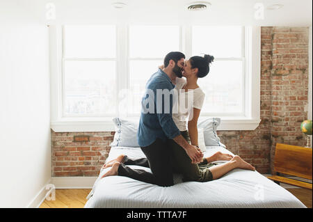 Romantic couple kissing while kneeling on bed at home - Stock Photo