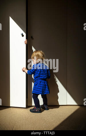 Full length of baby girl opening door while standing on carpet - Stock Photo
