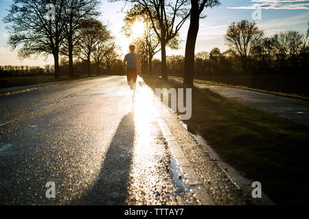 Rear view of male athlete running on road during sunset - Stock Photo