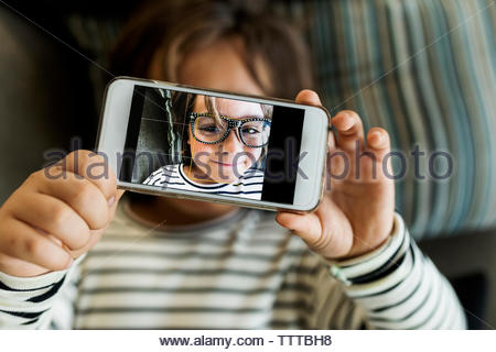 cute little boy with striped top taking a selfie laying in the sofa - Stock Photo